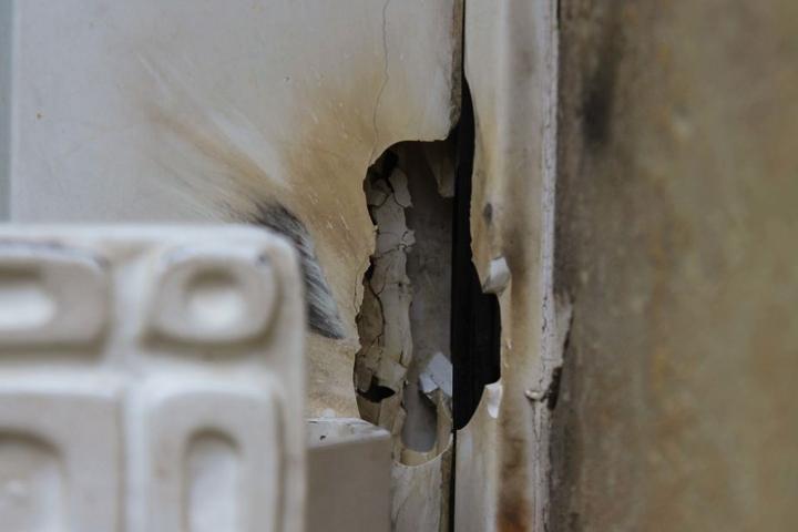 Die Beschädigung an der Eingangstür ist deutlich sichtbar.