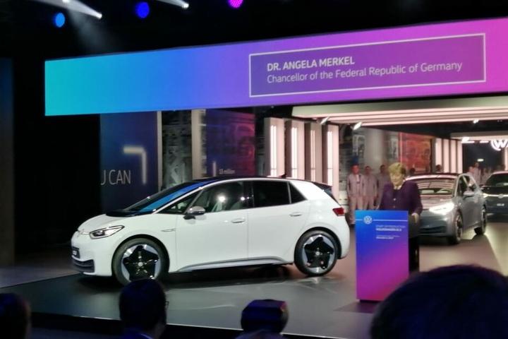 Die Bundeskanzlerin steht neben dem neuen Stromer von VW.