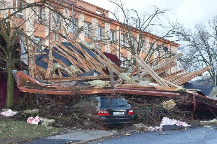 Ein Auto steckt unter den Trümmern fest, nachdem ein starker Wind durch die Stadt geweht ist.