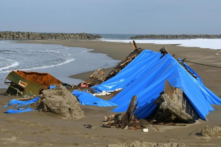 Das auseinandergebrochene Holzboot liegt am Strand in Kanazawa, Präfektur Ishikawa (Japan).