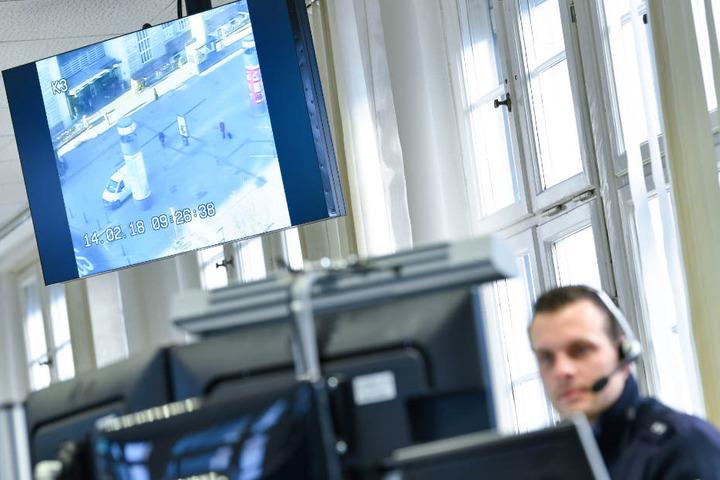 Ein Polizist sitzt im Februar 2018 im Führungs- und Lagezentrum an seinem Arbeitsplatz in Mannheim. Im Hintergrund hängt ein Monitor, auf dem das Bild einer Überwachungskamera am Hauptbahnhof zu sehen ist.