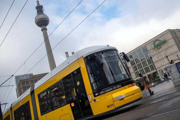 Eine Straßenbahn der Berliner Verkehrsbetriebe (BVG) fährt vor dem Fernsehturm über den Alexanderplatz.