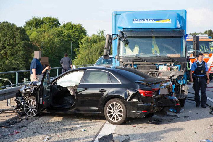 Ein Audi steht zertrümmert vor dem Lkw.