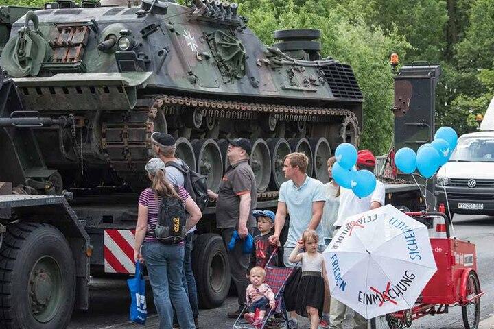 """Ein Mitglied der Partei Die Linke protestiert beim """"Tag der Bundeswehr"""" für Frieden neben einem Bergepanzer."""