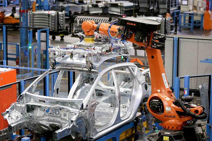 Roboter des Herstellers Kuka bauen im Ford Werk in Köln eine Karosserie zusammen.