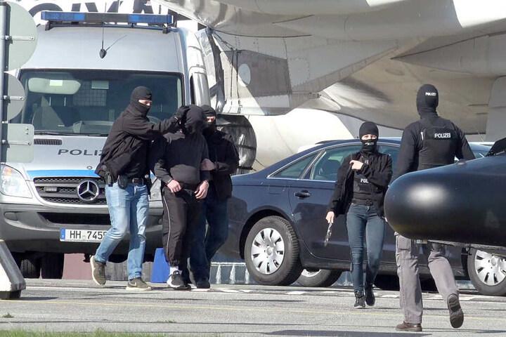 Ein mutmaßliches Mitglied der Terrormiliz IS (2.v.l.) wird auf dem Flughafen Hamburg zu einem Hubschrauber der Bundespolizei gebracht. Mit der Maschine wurde der Verdächtige nach Karlsruhe geflogen werden, wo ein Ermittlungsrichter beim Bundesgerichtshof