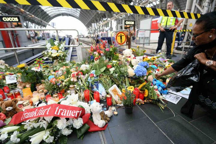 Eine Frau legt am Tatort am Gleis 7 des Hauptbahnhofs Blumen für den getöteten Achtjährigen ab.