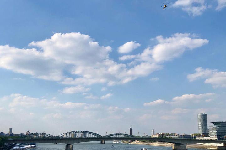 Ein Hubschrauber kreist über dem Rhein.