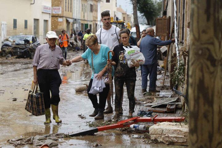 Anwohner gehen nach einem schweren Unwetter über eine mit Trümmern bedeckte Straße.