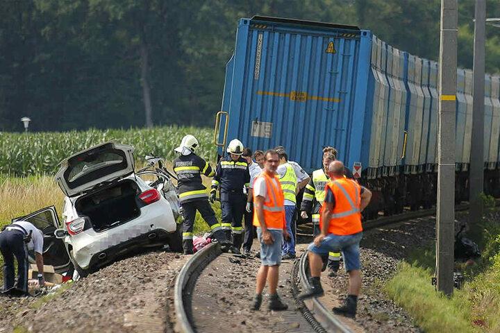 Rettungskräfte stehen am Unfallort. Bei dem Crash wurden der Fahrer des Autos sowie seine Beifahrerin tödlich verletzt.