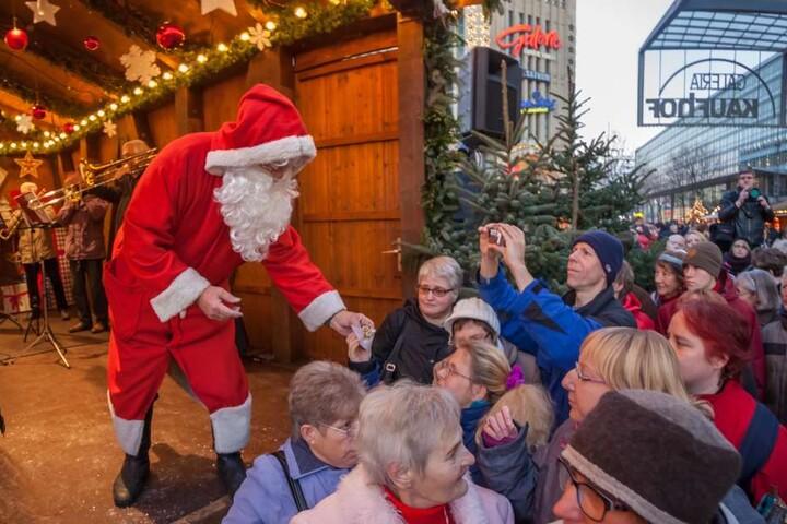 Der Weihnachtsmann verteilt nach der Eröffnung den Christstollen.