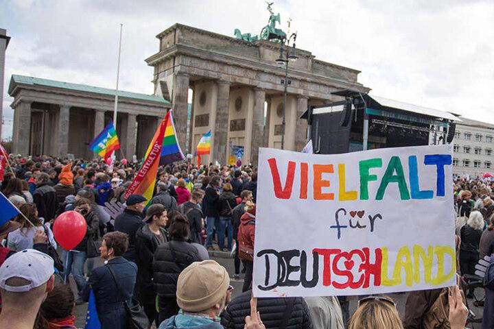 """Eine Frau mit einem Transparent """"Vielfalt für Deutschland"""" hat sich mit zahlreichen Menschen am Brandenburger Tor versammelt."""