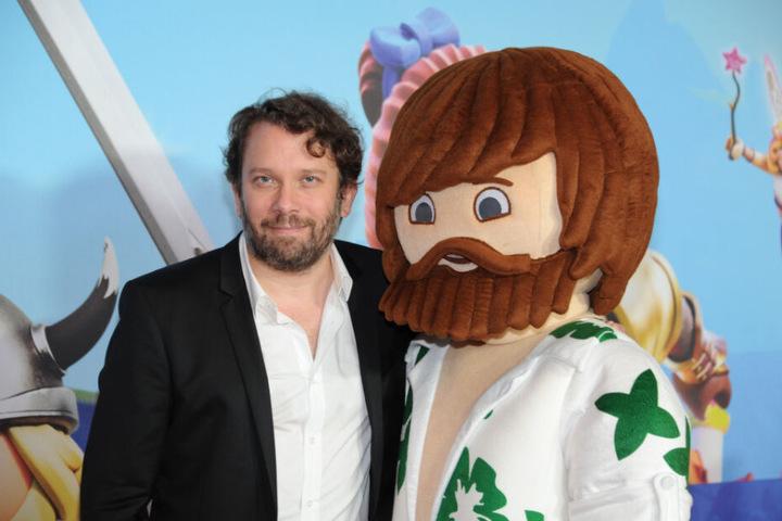 """Der Schauspieler Christian Ulmen steht bei seiner Filmpremiere""""Playmobil - der Film"""" mit der Playmobil Figur """"Del"""" im Mathäser Kino in München."""