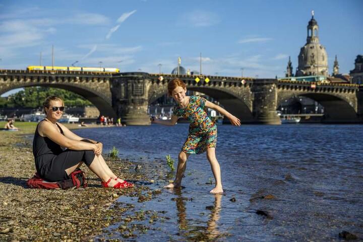 Bei der Gluthitze verwandelt sich die Elbe langsam in ein Rinnsal: Ana (10)  und Dani Doege (37) aus Berlin entspannen am Elbufer.