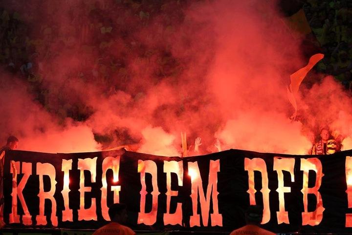 """Dortmundfans brannten. mehrfach Pyro ab. Hier hinter dem Banner """"Krieg dem DFB""""."""