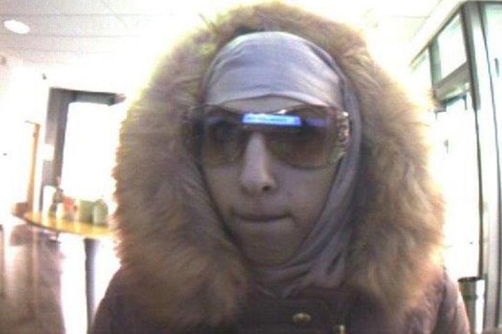 Mit Hilfe einer Sonnenbrille, versucht die Verbrecherin ihr Gesicht zu schützen.
