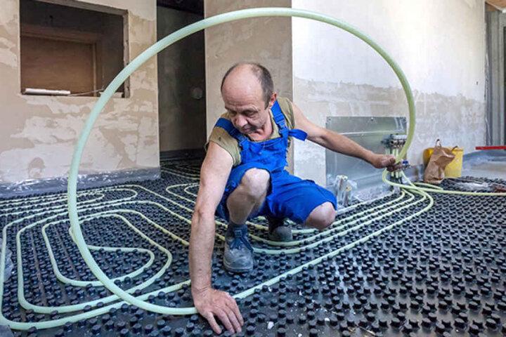 Thomas Mehnert (50) verlegt die neuen Rohre für die Fußbodenheizung in den Duschen.