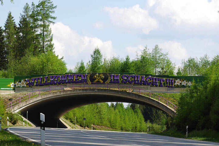"""Die Brücke über den Autobahn-Zubringer in Richtung Aue. Darüber steht """"Willkommen im Schacht"""". Wer als Gegner ins Stadion will, muss hier durch."""