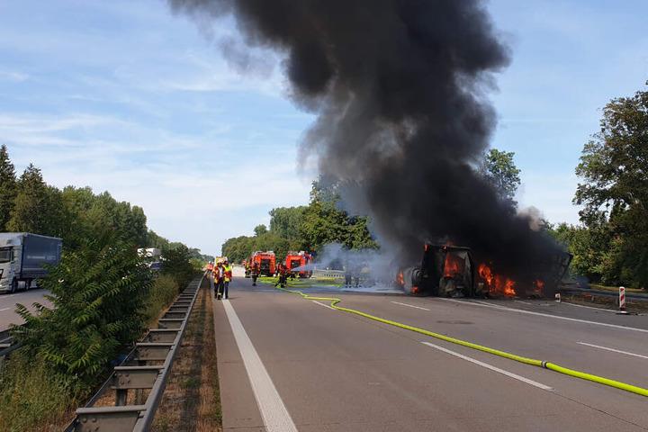 Feuerwehrleute löschen das brennende Fahrzeug.