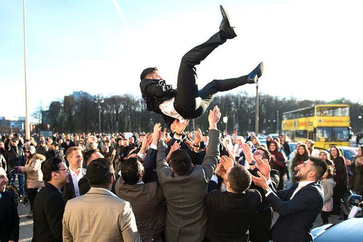 Bei einer türkischen Hochzeitsfeierlichkeit in Berlin werfen Männer den Bräutigam in die Luft (Symbolbild).