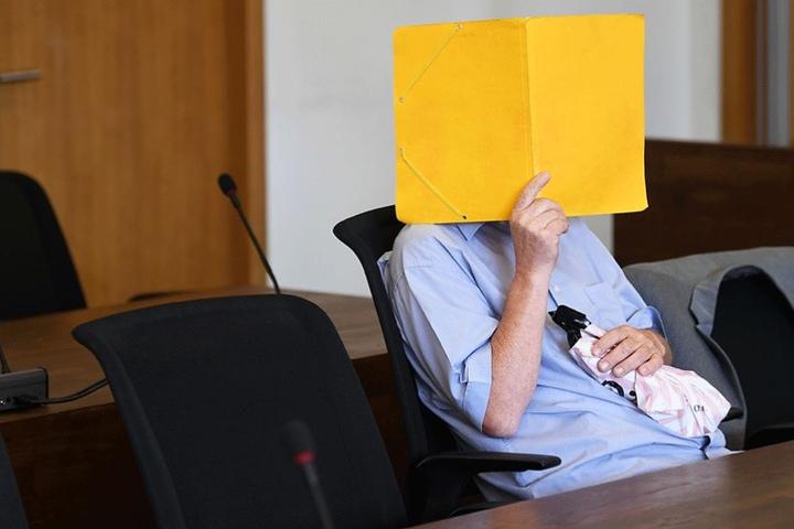 Der Angekläffte verbirgt sein Gesicht zum Prozessauftakt hinter einem Ordner.