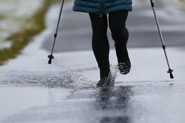Eine Spaziergängerin läuft auf einem überfluteten Weg bei Unlingen (Kreis Biberach).