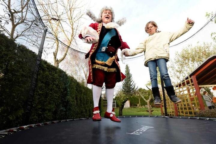 Kurfürst August hopst mit Ronja im Trampolin - Perücke und Rockschöße fliegen in die Luft.