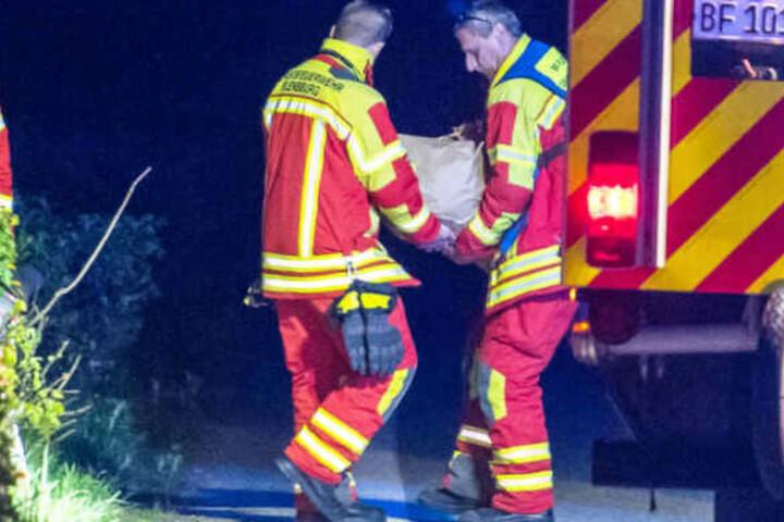Helfer der Feuerwehr tragen einen der großen Stein von der Unfallstelle.