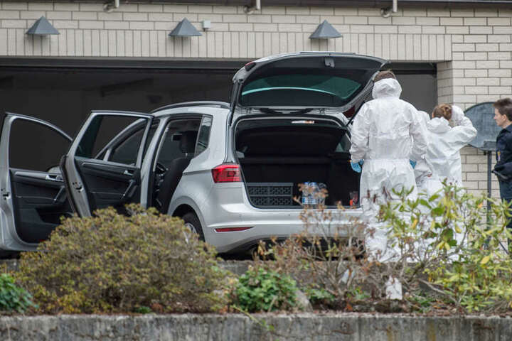 Mitarbeiter der Spurensicherung stehen vor der Garage des Hauses im Mörlenbach.