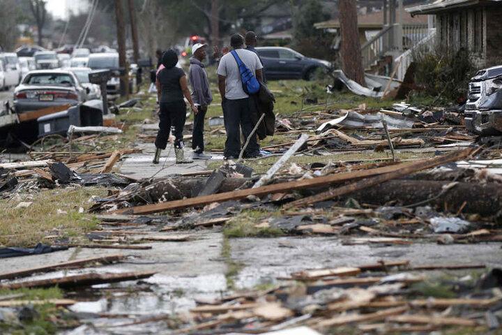Anwohner stehen zwischen den Resten ihrer zerstörten Häusern.