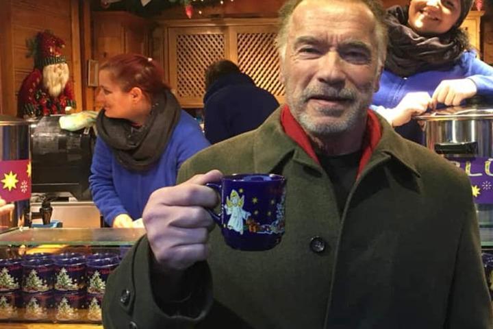 Arnold Schwarzenegger ließ sich auf dem Christkindlmarkt in München vor einem Stand fotografieren.
