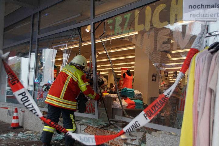 Ein Feuerwehrmann vor dem kaputten Schaufenster.