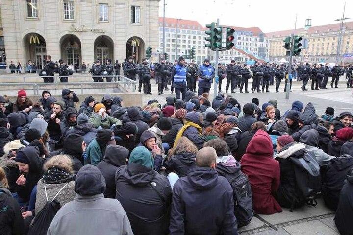 Am Altmarkt hat sich eine Sitzblockade formiert. Die Polizei versucht die Gegendemonstranten dazu zu bewegen, die Strecke frei zu geben.
