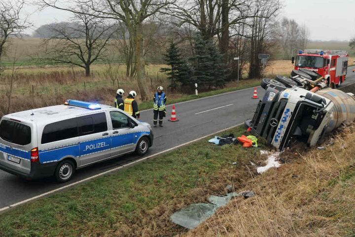 Einsatzkräfte von Polizei und Feuerwehr stehen an der Unfallstelle.