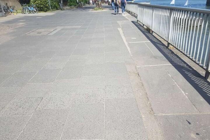 """Schräge Verschnitte, graue Platten und teils lose Platten ebnen die """"Flaniermeile"""" am Rhein."""