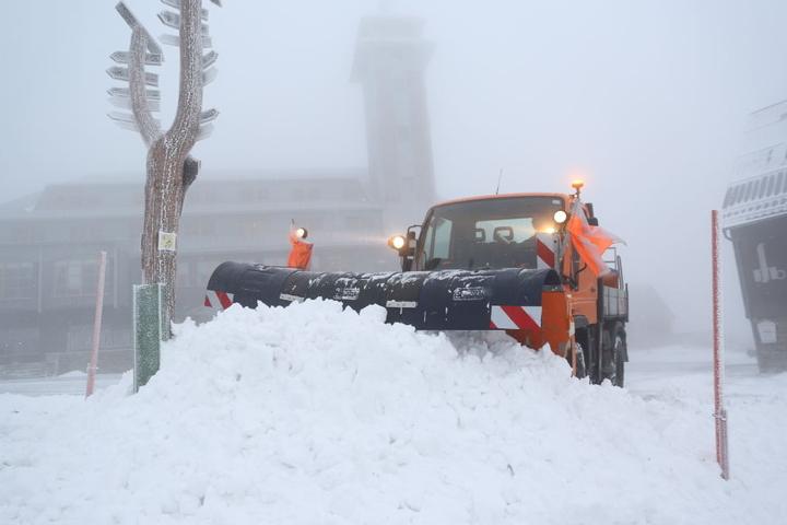 Auf dem Fichtelberg ist ordentlich was runtergekommen: Ein Schneepflug schiebt den Neuschnee auf einen großen Haufen.