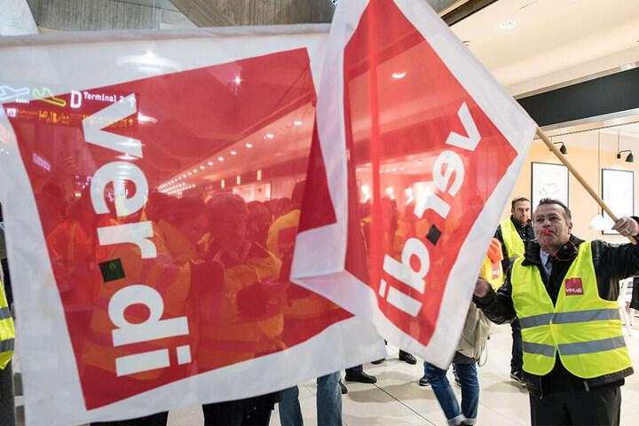 Hier wurde schon gestreikt: Mitglieder der Gewerkschaft Verdi stehen am 10.01.2019 mit Fahnen am Flughafen Köln/Bonn in einem Terminal. An den Airports Köln/Bonn, Düsseldorf und Stuttgart streikte das Sicherheitspersonal jeweils ganztägig.