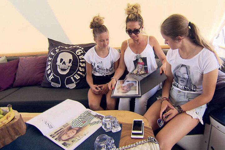 Carmen zeigt ihren Töchtern Shanias Model-Mappe.