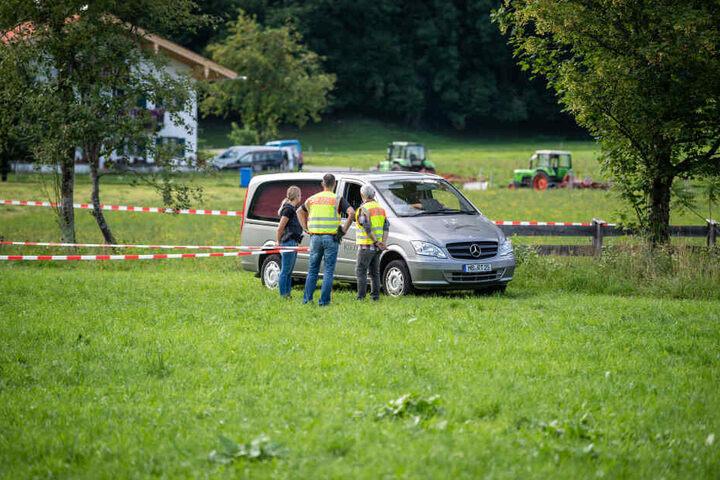 Das Fahrzeug eines Bestatters verlässt im Ortsteil Scharling einen abgesperrten Bereich an einem Bachlauf.