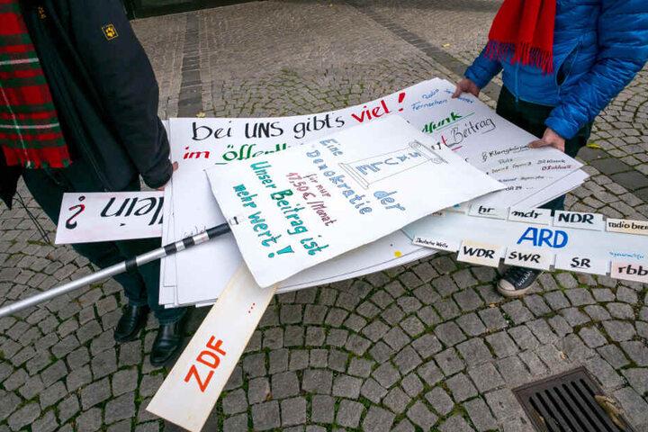 Diverse Protestplakate werden von zwei Männern vor das Funkhaus des Bayerischen Rundfunk (BR) getragen.