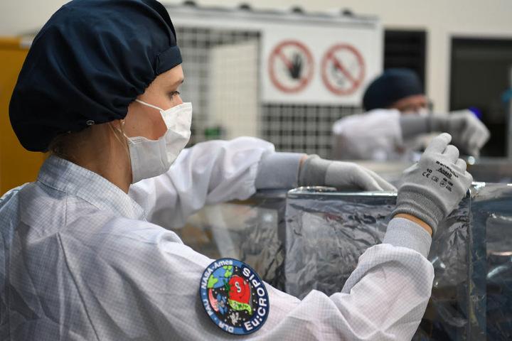 """Eine Mitarbeiterin des DLR verpackt den Forschungssatelliten """"Eu:CROPIS""""."""