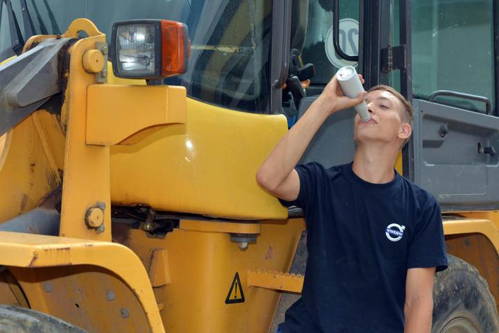 Niklas Kloß (22) trinkt auf einer Baustelle einen Fleisch-Drink in einer Flasche.