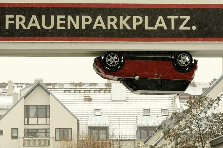 """Ein Auto hängt verkehrt herum an einem Durchgang in München: Über der Installation, die für einen Autohersteller wirbt, steht provokant die Aufschrift """"Frauenparkplatz""""."""