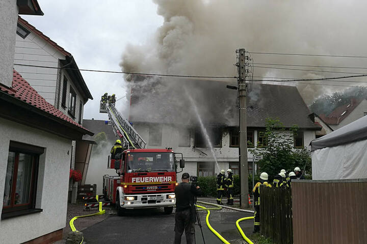 Das Feuer wütet unter dem Dach des Mehrfamilienhauses.