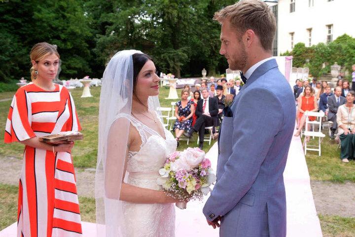 Mit dem Brautstrauß in der Hand schaut Emily zu Paul.
