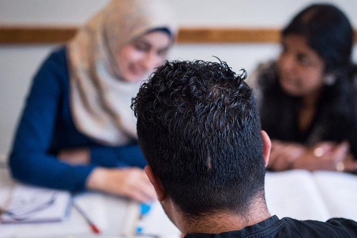 Drei Schüler nehmen in einer Volkshochschule an einem Integrationskurs teil.