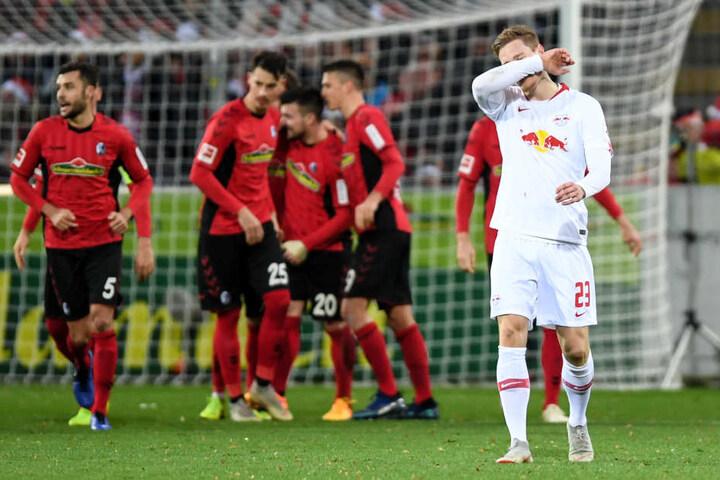 Während sich Linksverteidiger Marcel Halstenberg (r.) enttäuscht mit dem Arm durchs Gesicht fährt, feiern die Freiburger das 2:0 durch Gian-Luca Waldschmidt.