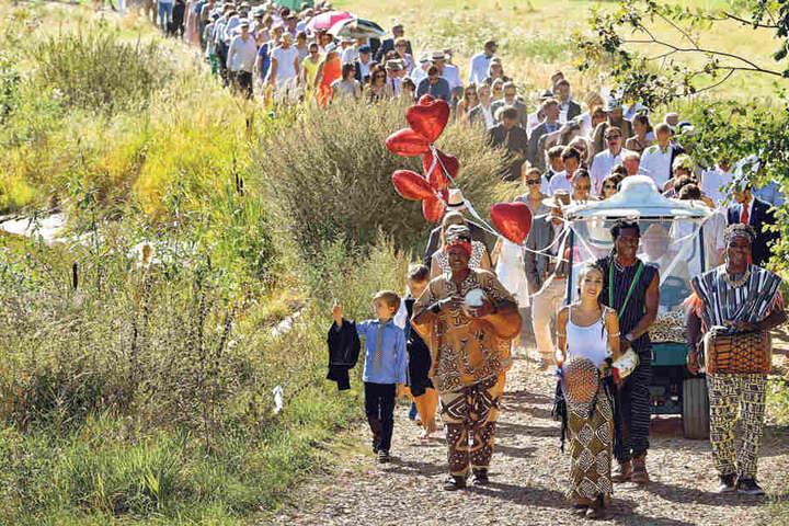Afrikanische Musiker führen den Hochzeitszug zum Safari-Camp an. Gleich  hinter ihnen fährt das vermählte Paar im Golfwagen.