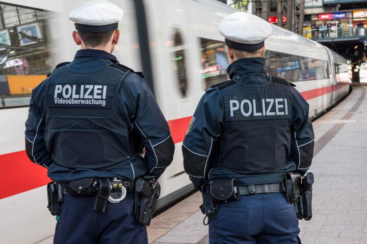 Zwei Bundespolizisten stehen am Bahnhof, während ein ICE vorbeifährt.