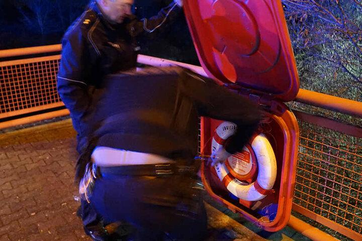 Polizeibeamte bringen den Rettungsring wieder an seinen Platz.